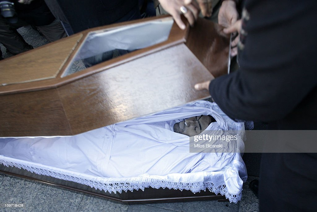 A lid of a coffin is moved above the body as members of an Athen's Pakistani community gather near the remains of 27-year-old Pakistani migrant who was a victim of an alleged racism-fuelled crime on January 19, 2013 in Athens, Greece. Hundreds of Greeks and other nationals marched peacefully against racism on January 19. Long standing as a hub for immigration from the Middle East, Africa and Asia, Greece is under pressure with racial issues as the economic crisis warps the burdens of blame in struggling communities.