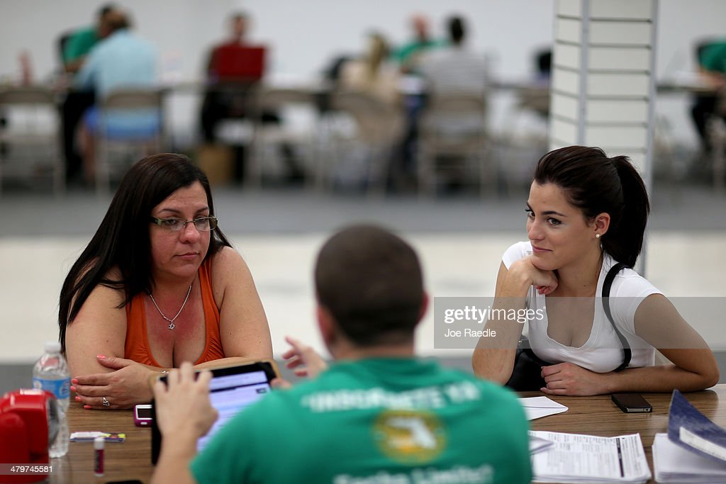 Lidice Bacallao (L) andYislaine Diaz sit with Amaury Garcia an insurance agent from Sunshine Life and Health Advisors as they purchase individual health insurance policies under the Affordable Care Act at a store setup in the Mall of Americas on March 20, 2014 in Miami, Florida. The owner of Sunshine Life and Health Advisors, Odalys Arevalo, said she has seen a surge in people, some waiting up to 3 hours or more in line, trying to sign up for the Affordable Care Act before the open enrollment period for individual insurance ends on March 31.