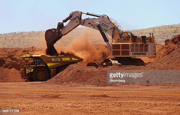A LiebherrInternational Deutschland GmbH excavator loads iron ore onto a Caterpillar Inc 793F autonomous haul truck at the Kings mine site at...