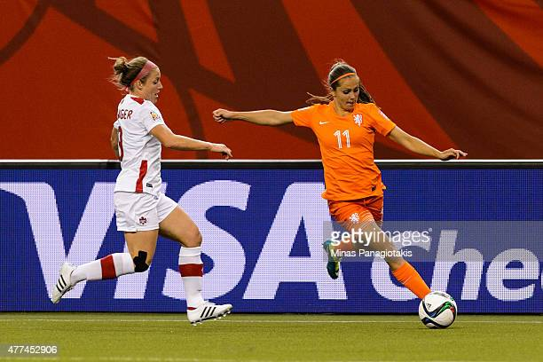 Lieke Martens of the Netherlands moves the ball past Josee Belanger of Canada during the 2015 FIFA Women's World Cup Group A match at Olympic Stadium...