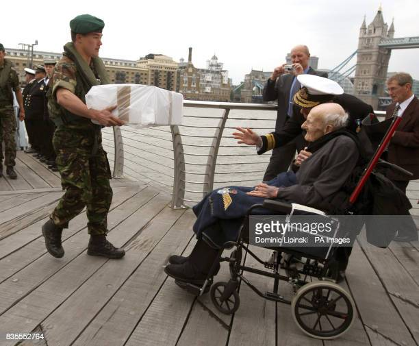 Lieutenant Andy Pugsley from the Royal Marines delivers a birthday cake to Britain's oldest man and oldest surviving First World War veteran Henry...