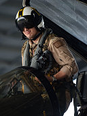 Lieutenant Christopher Pagenkopf a pilot in the United States Navy VFA115 squadron climbs into the cockpit of a FA/18E Super Hornet while it sits in...