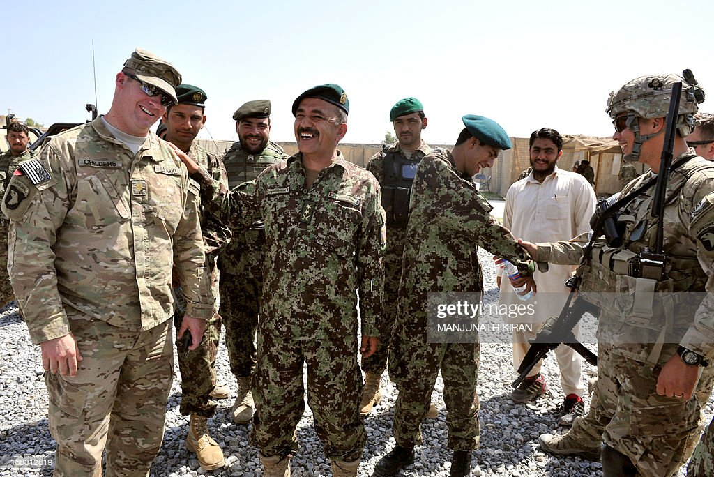 Lieutenant Colonel of 201st Selab, 4th Brigade, 4th Battalion, of the Afghanistan National Army (ANA) Commander Asadullah (C) laughs next to US Major Childres (L) of the Field Artillery Battery of 4th Kandak, 4th Brigade, 201st Corps of Combined Team Bastogne (Nangarhar), 1st Brigade Combat Team, 101st Airborne Division (Air Assault) during a training session of ANA soldiers at the Shinwar Forward Base in the province of Nangarhar on April 11, 2013. The Field Artillery Battery of 4th Kandak has been training Afghan soldiers in using artillery to support their Afghan National Army.