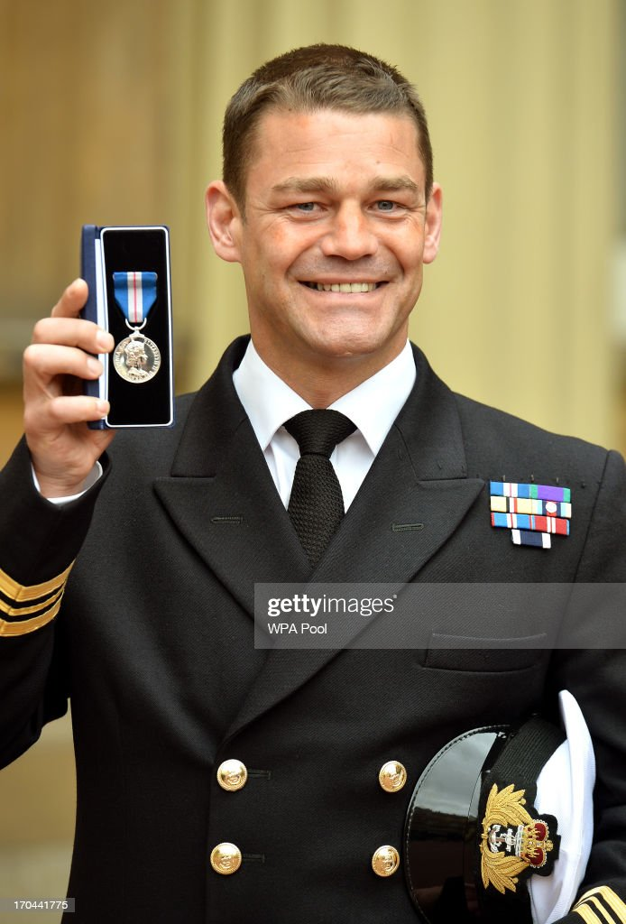 Lieutenant Commander, Al Nekrews proudly holds his Queen's Gallantry Medal, after it was presented to him by Queen <a gi-track='captionPersonalityLinkClicked' href=/galleries/search?phrase=Elizabeth+II&family=editorial&specificpeople=67226 ng-click='$event.stopPropagation()'>Elizabeth II</a>, at the Investiture ceremony at Buckingham Palace on June 13, 2013 in London, England.