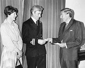 Lieutenant Commander Doug Taylor with his wife receiving a check for £25000 for inventing the 'skijump' take off ramp for Royal Navy ships presented...