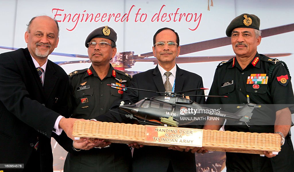 Lieutenant General of the Indian Army, Narendra Singh, (R), HAL Chairman, R.K. Tyagi,(2R), Major General, AOG (Army Aviation) General P.K. Bharali, (2L) and Managing Director of HAL, P. Sounderajan pose for a photograph during the handing over of the Light Combat Helicopter (LCH), 'Rudra' to the Indian Army on the third day of the 9th edition of the Aero India 2013 at Yelahanka Air Force station in Bangalore on February 8, 2013. India, the world's leading importer of weaponry, opened one of Asia's biggest aviation trade shows February 6 with Western suppliers eyeing lucrative deals and a Chinese delegation attending for the first time. AFP/Manjunath KIRAN