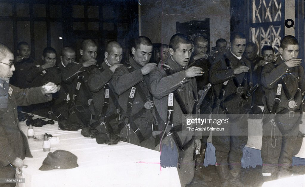 Lieutenant Kunio Ishida of the Special Attack Unit Hakko 7th unit Tanshin leader and other pilots drink glass of sake before the kamikaze attack...