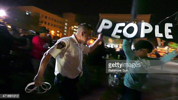 A lieutenant with the Baltimore Police pushes a woman away as police roust protesters off the City Hall lawn at the start of the daily curfew in...