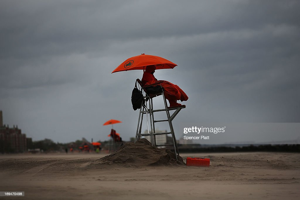 A Life guard is viewed on a chilly afternoon at the beach at Coney Island on the first weekend of city beaches re-opening to the public on May 25, 2013 in the Brooklyn borough of New York City. While warmer weather and sunny skies are expected for the remainder of the holiday weekend, cool temperatures and rain kept area beaches largely empty.