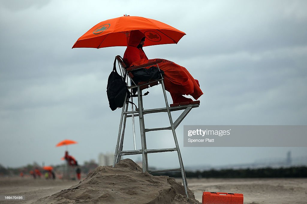 Life guard Paul Shmidt tries to stay warm on a chilly afternoon at the beach at Coney Island on the first weekend of city beaches re-opening to the public on May 25, 2013 in the Brooklyn borough of New York City. While warmer weather and sunny skies are expected for the remainder of the holiday weekend, cool temperatures and rain kept area beaches largely empty.