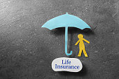 Paper person under an umbrella with Life Insurance message