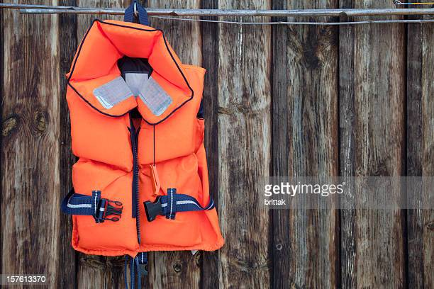 Life jacket for a child against an old wooden wall.
