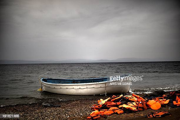 Life jackets and a boat that were used by refugees and migrants to cross the Aegean sea from Turkey lie abandoned on a beach on the Greek Island of...