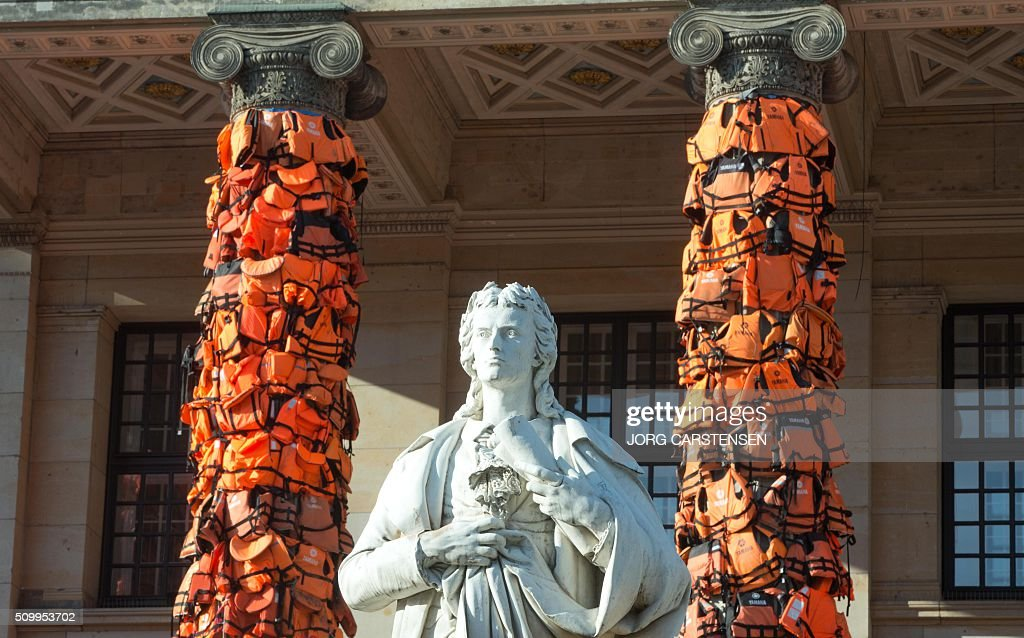 Life jackets are fixed at the columns of the Konzerthaus concert hall at Berlin's Gendarmenmarkt place on February 13, 2016 to complete a temporary installation by Chinese artist Ai Weiwei. Ai Weiwei aims to draw attention to the terrible fate of refugees who were drowned on their way to Europe. The live vests were provided by the Greek island of Lesbos. / AFP / dpa / Jörg Carstensen / Germany OUT / RESTRICTED TO EDITORIAL USE - MANDATORY MENTION OF THE ARTIST UPON PUBLICATION - TO ILLUSTRATE THE EVENT AS SPECIFIED IN THE CAPTION