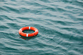 orange lifebuoy on the waves as the concept of salvation