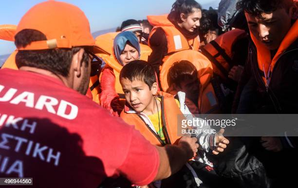 A lifeguard assists a young boy as he disembarks from a rubber dinghy as he arrives along with other migrants and refugees on the Greek island of...
