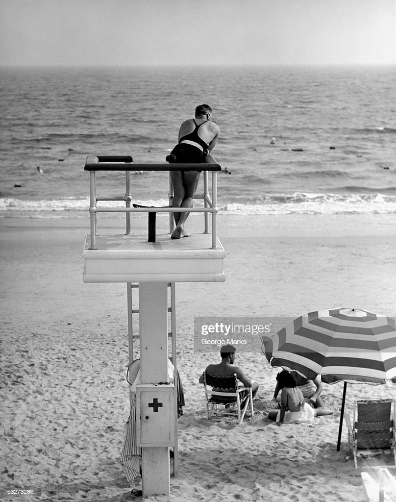 Life-guard looking over water : Stock Photo