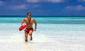 Male lifeguard running in turquoise waters in the Maldives