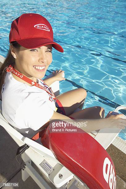 Lifeguard sitting in chair at swimming pool