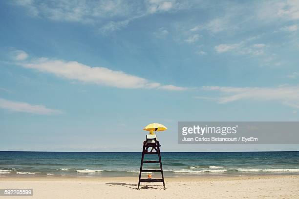 Lifeguard Sitting On Chair At Beach Against Sky