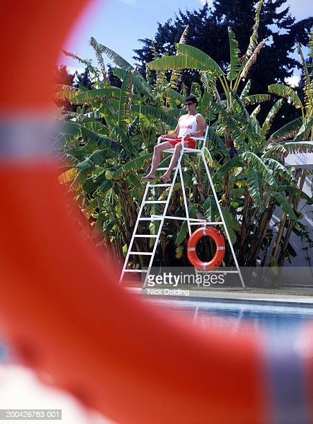 Lifeguard sitting on tower at pool, outdoors