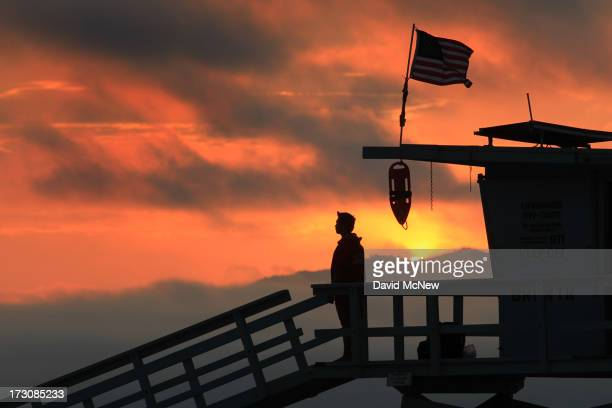 A lifeguard stands watch at sunset on Independence Day weekend at Venice Beach on July 5 2013 in Venice California An estimated 16 million people...