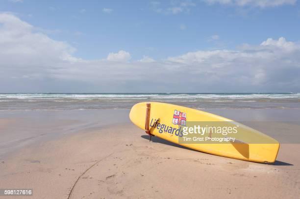 RNLI Lifeguard Surfboard on an empty beach