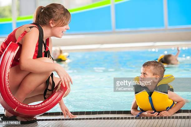 Maître-nageur former un petit garçon apprendre à nager
