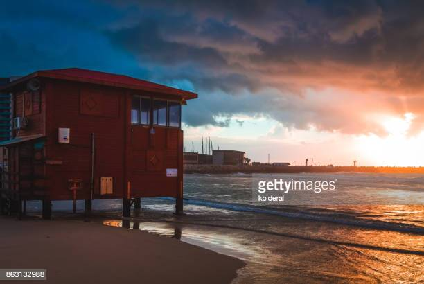 Lifeguard tower against Scenic sunset on empty Mediterranean beach during stormy winter evening