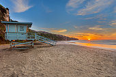 A lifeguard tower sits on the beach at sunset with the sun over the ocean.