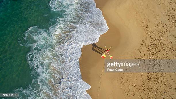 Lifeguard walking on beach with flags