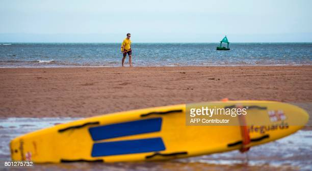 A lifeguard walks along a sand bank at low tide in the estuary of the river Exe as it runs into the English channel by Exmouth in south west England...