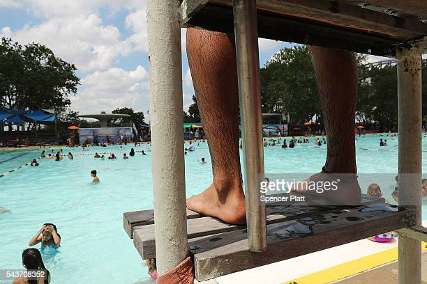 A lifeguard watches as people enjoy a hot afternoon at the Astoria Pool in the borough of Queens on the opening day of city pools on June 29 2016 in...
