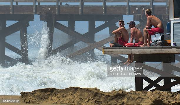 Lifeguards keep watch as big waves crash ashore near the pier at Seal Beach California on August 27 where some overnight flooding occurred as the...
