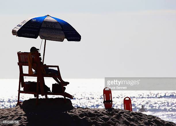 Lifeguards watch surfers who enjoy four to six foot swells off the Atlantic Ocean on August 28 2014 in Long Beach New York Hurricane Cristobal is...