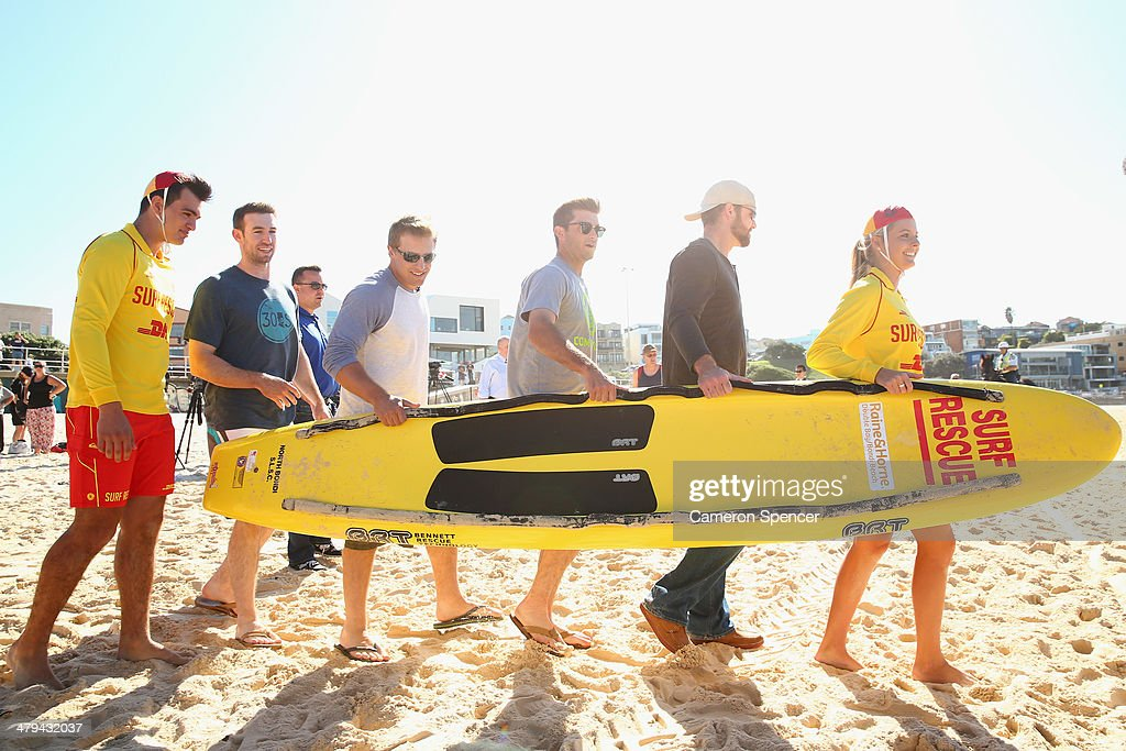 Lifesaver Sophie Thomson carries a paddleboard with Chris Withrow, <a gi-track='captionPersonalityLinkClicked' href=/galleries/search?phrase=Drew+Butera&family=editorial&specificpeople=4175498 ng-click='$event.stopPropagation()'>Drew Butera</a>, Tim Federowicz and Mike Baxter of the Los Angeles Dodgers during a Los Angeles Dodgers players visit at Bondi Beach on March 19, 2014 in Sydney, Australia.