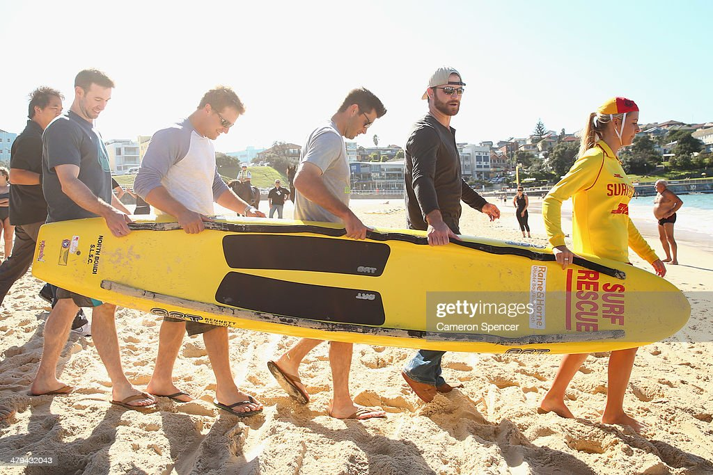 Lifesaver Sophie Thomson carries a paddleboard with Chris Withrow, Drew Butera, Tim Federowicz and Mike Baxter of the Los Angeles Dodgers during a Los Angeles Dodgers players visit at Bondi Beach on March 19, 2014 in Sydney, Australia.