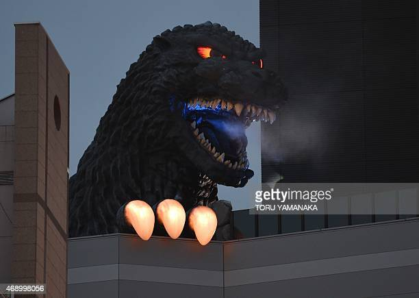 A lifesize Godzilla head on a balcony of the eighth floor of Hotel Gracery Shinjuku expels smoke from its mouth during the official unveiling...