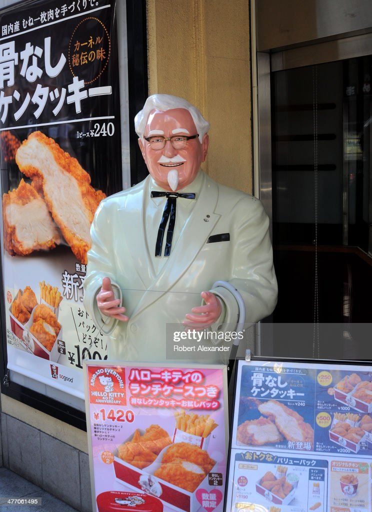 A lifesize plastic statue of Col Harlan Sanders stands in front of a KFC restaurant in the Shibuya district of Tokyo Japan