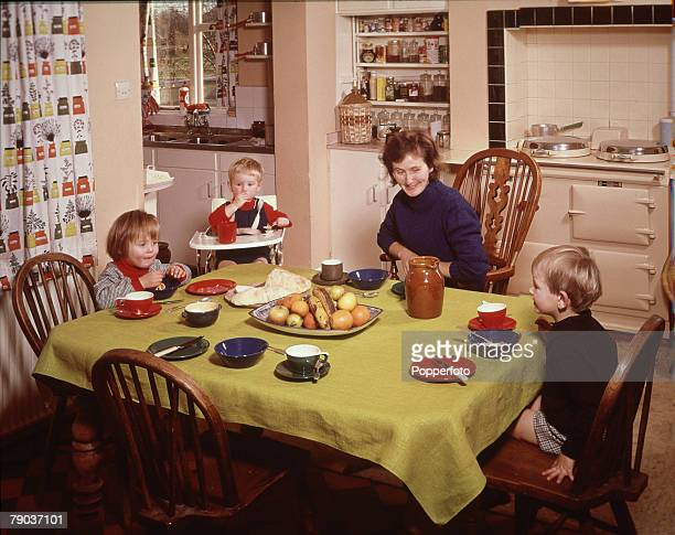 Lifestyle A Family scene showing a mother sitting at the dinner table with three children one in a high chair eating