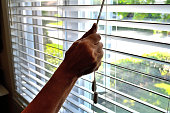 Lifestyle...This close up shot, shows an arm lowering or opening a bedroom window shade.