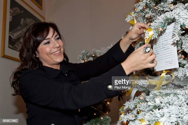 Lifestyle Expert Kelley Moore puts some finishing touches on the Christmas tree decor she designed for Microsoft's 'A Salute to Our Troops' at Fisher...