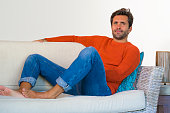 lifestyle home portrait of young attractive and happy 30s man smiling relaxed and comfortable sitting at living room sofa couch in his modern apartment cheerful and positive in success concept