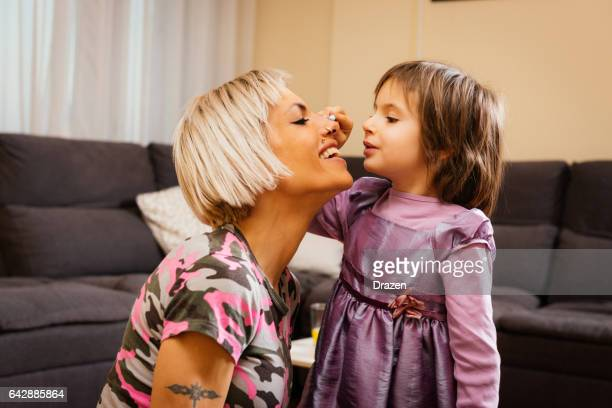 Lifestyle of modern Eastern European family - tattooed single mother and daughter at home enjoying internet content