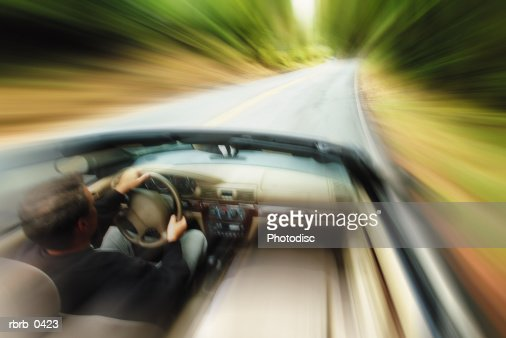 lifestyle photograph of a caucasian man driving fast down a road in a convertible : Stockfoto