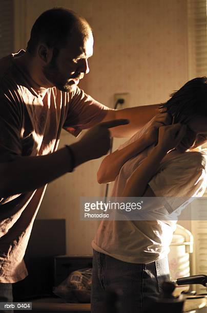 lifestyle photograph of a young caucasian couple as the man becomes angry and abusive