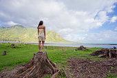 Lifestyle portrait of an attractive Hawaiian woman wearing a flower dress at Kahana Bay on Oahu Hawaii.
