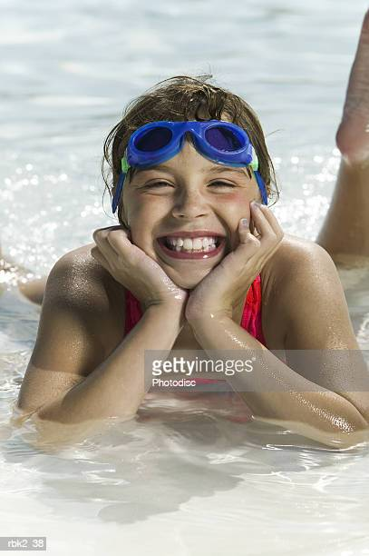 lifestyle portrait of a female child in a pink swimsuit and goggles as she lays in a pool and smiles brightly