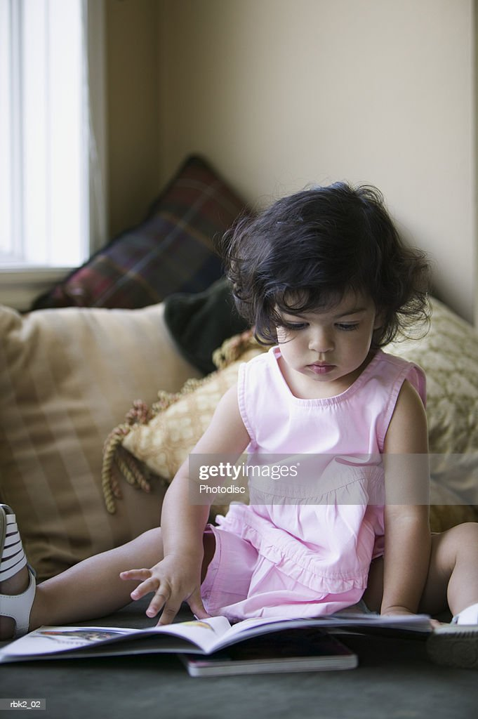 lifestyle portrait of a female toddler in a pink dress as she sits on a couch and reads a book