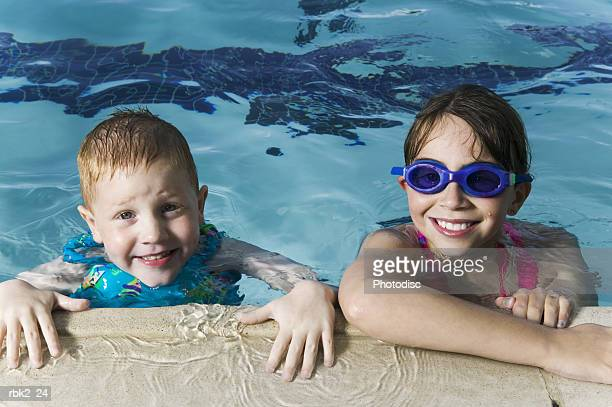 lifestyle portrait of a two young children as they play at the edge of a swimming pool and smile